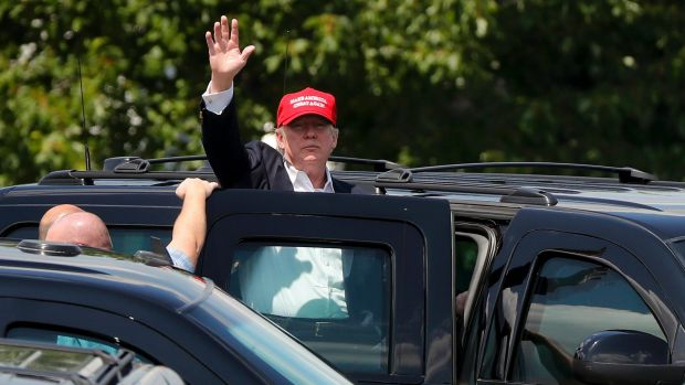 President Trump waves to spectators outside his residence at the Trump National Golf Club.