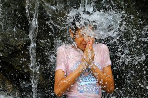 A girl stands under a water fall like a meditating Buddhist monk as she plays in the water fountain at Asuka Park in ...