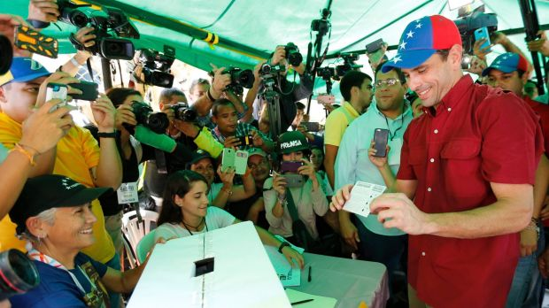 Opposition leader Henrique Capriles shows a ballot during a symbolic referendum in Caracas, on Sunday.