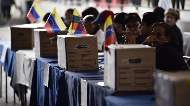 Polling officials wait for voters during the symbolic Venezuelan plebiscite in Caracas called by opposition parties.