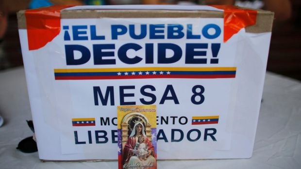 "A image of Virgin Mary decorates the front of a box that reads in Spanish ""The People decide, table 8"" at a poll station ..."