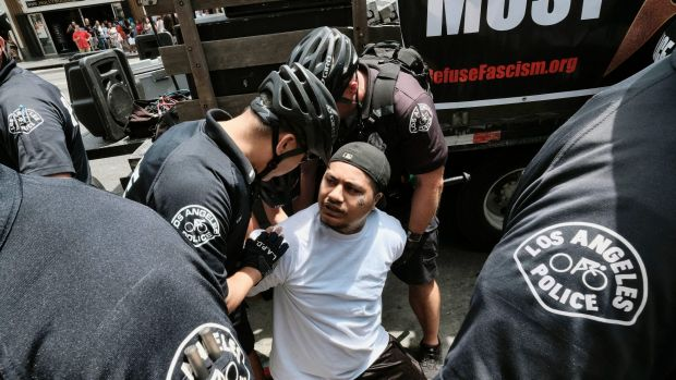 A Trump supporter is arrested by Los Angeles Police officers after getting into a fight with an anti-Trump protester in ...