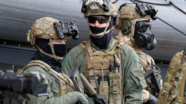 Armed and masked special forces troops at the announcement of the government's new policies on military involvement in ...