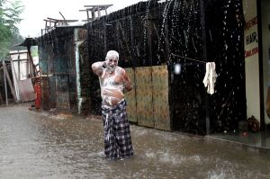 In this Tuesday, July 11, 2017 file photo, a man soaps himself up and takes bath during monsoon rains in Allahabad, ...