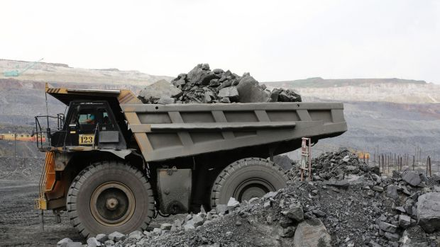 A truck carries excavated iron ore.