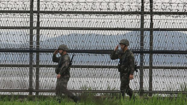 South Korean army soldiers salute as they patrol along the barbed-wire fence in South Korea's Paju, near the border with ...