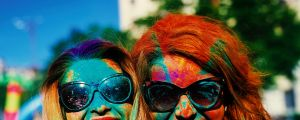 two friends portrait with colorful powder on their faces enjoying happy times in the holi color festival. satjul22cover