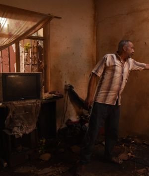 Nadhm Hamid points to the damaged wall caused by a chemical weapon that came through the roof of his families home ...