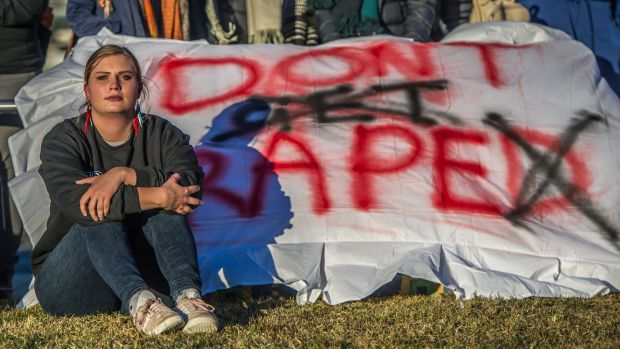 Sexual assault victim Freya protests on the lawns outside Parliament House.