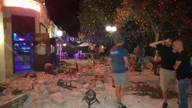 A man lies on the ground as other tourists stand outside a bar after an earthquake on the Greek island of Kos early on ...