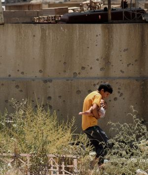 A teenage boy protects a baby as he runs to safety after fleeing Islamic State during the offensive to retake West ...