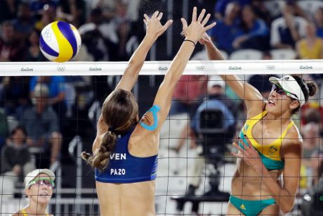 Australia's Taliqua Clancy, right, hits over Venezuela's Olaya Pazo during a women's beach volleyball match at the 2016 ...