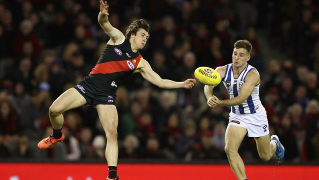 Andrew McGrath of the Bombers and Shaun Atley of the Kangaroos compete for the ball.