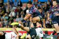 Power play: Jason Taumalolo steamrolls the Warriors defence.
