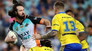 Aaron Woods of the Tigers is tackled by the Eels defence during the round 20 NRL match between the Wests Tigers and the ...