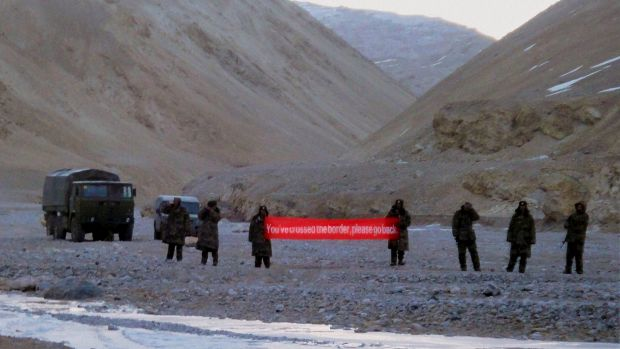 """Chinese troops hold a banner which reads """"You've crossed the border, please go back"""" in Ladakh, India."""
