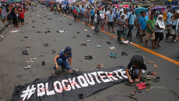 "Protesters scatter pairs of slippers and shoes to symbolise victims of President Rodrigo Duterte's ""war on drugs""."