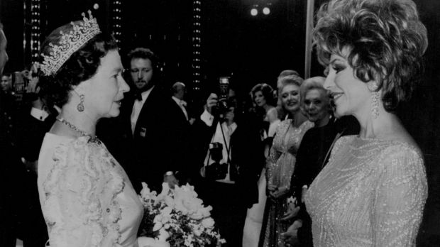 Joan Collins meets Queen Elizabeth II at London's Theatre Royal in 1985.