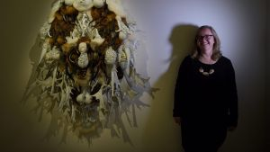 Anne Ryan, Curator of The Wynne Prize stands next to a sculpture by Juz Kitson called 'That which provides safety and ...