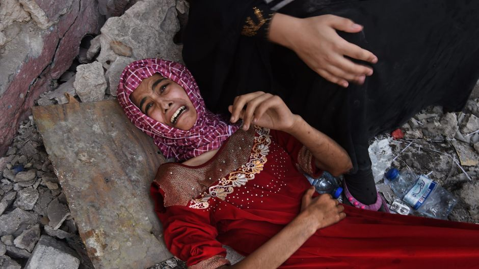 Fifteen year old Tabarek who is wounded and can no longer walk lies at the feet of her family as they rest for a few ...