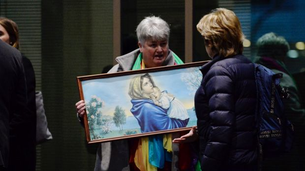 Julie Cameron holds a painting of the Virgin Mary and child outside the Melbourne Magistrates Cout.