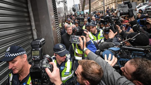 Police help George Pell through the 100-strong crush of national and international media in July.