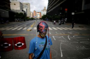 A demonstrator wearing a mask adorned with rosaries stands near a barricade during a 48-hour general strike beginning ...