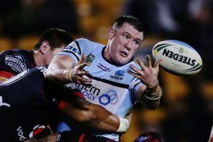 Leading from the front: Paul Gallen throws an offload against the Warriors.