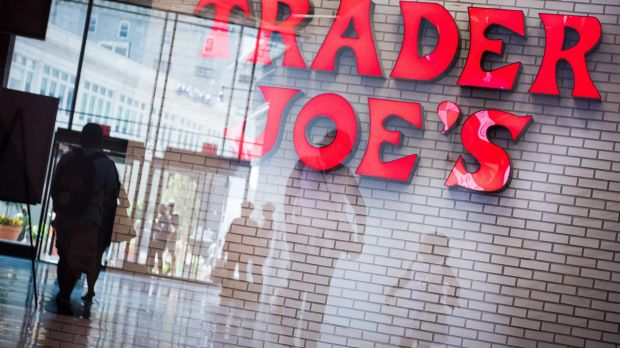 Shoppers are reflected in a window in front of Trader Joe's grocery store in New York.