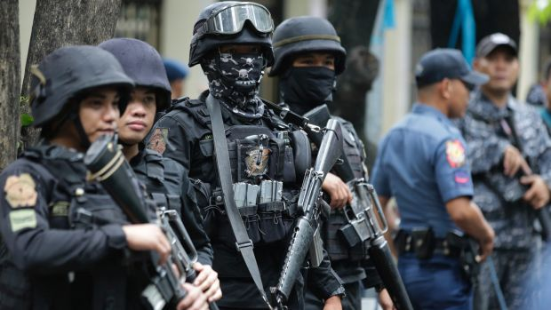 Armed police keep watch as men suspected of being Marawi militants arrive at the Department of Justice in Manila in July.