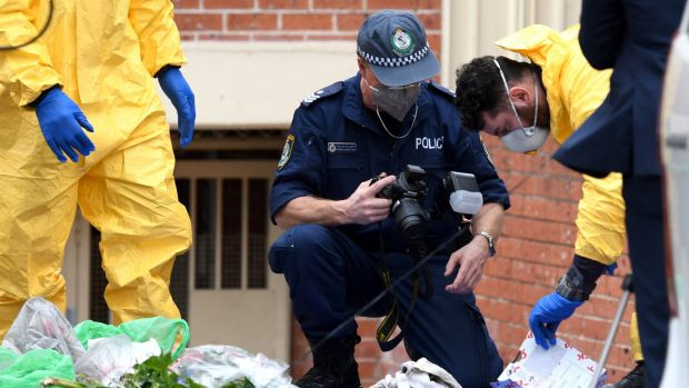 Police examine items outside a Lakemba unit on Monday as part of their investigation into an alleged terrorism plot.