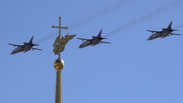 Sukhoy SU-24M military jets fly over a gilded weather vane in the form of an angel, fixed atop a spire of the Saints ...