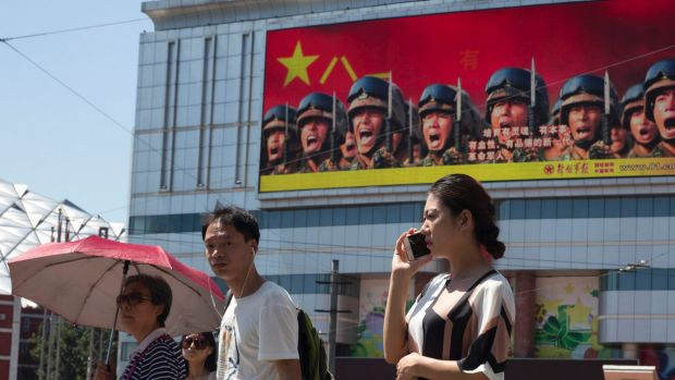 Beijing is intensifying its warnings to Indian troops to get out of a contested region. People wait at a traffic ...