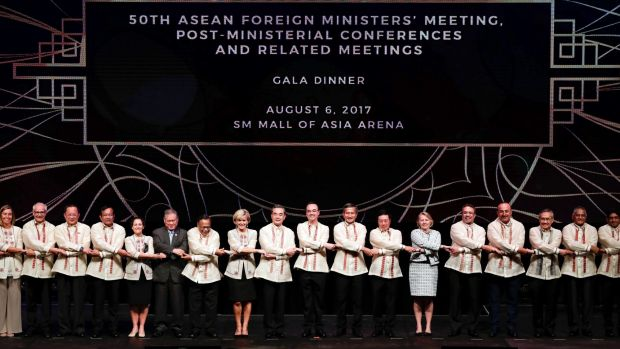 Foreign ministers from Southeast Asia and their dialogue partners link arms during the gala dinner of ASEAN foreign ...