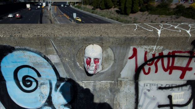 One of the mysterious stone faces on the bridge over CityLink.