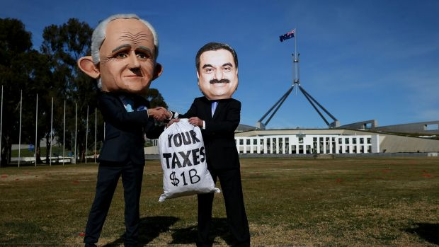 Protestors wearing suits resembling Prime Minister Malcolm Turnbull and Adani chief, Gautam Adani, take part in a ...