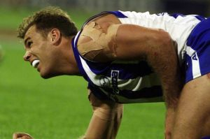 Wayne Carey winces in pain from a shoulder injury. He played on.