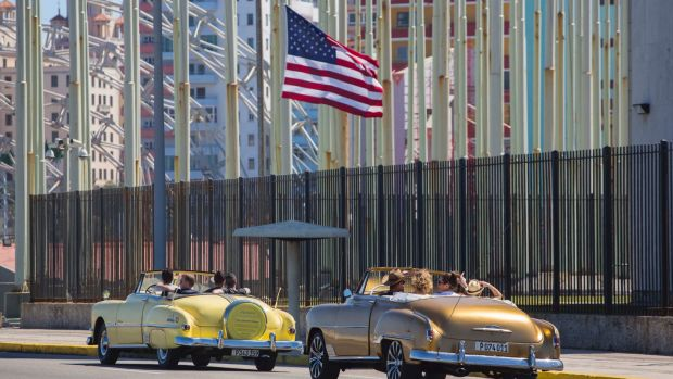 Tourists ride vintage American convertibles as they pass by the United States embassy in Havana, Cuba, as tensions eased ...