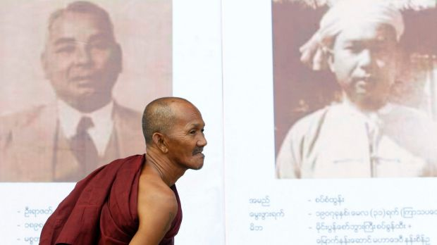 A Buddhist monk views portraits of Myanmar's Independence hero General Aung San.