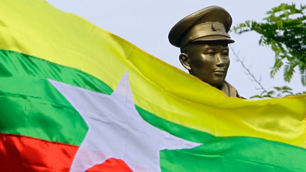 The Myanmar national flag flies in front of a statue of General Aung San during a ceremony marking the 70th anniversary ...