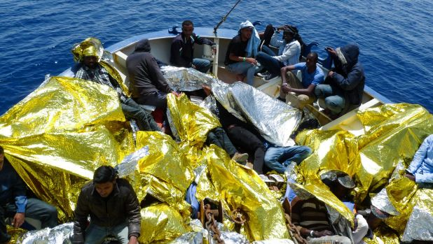 Rescued migrants are given thermal blankets.