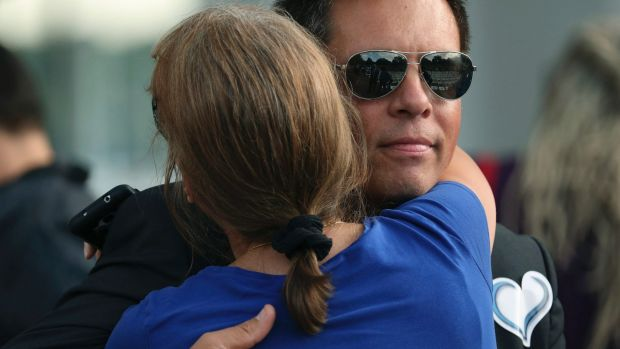 Don Damond gets a hug from a supporter shortly after he arrived for a memorial service.