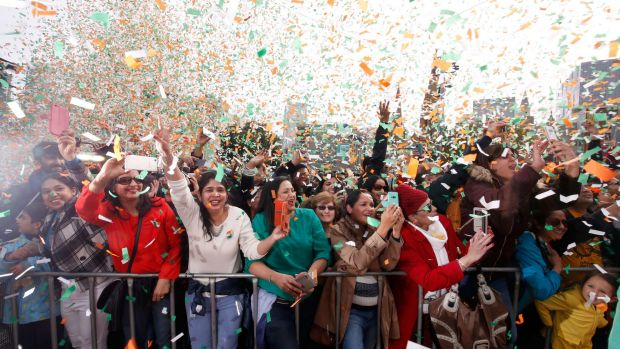 Crowds are showered in saffron, white and green confetti, the colours of the Indian flag, during Aishwarya Rai ...