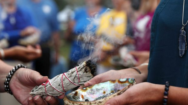 Volunteers take part in a Native American spiritual burning of sage during the memorial service for Justine Damond at ...