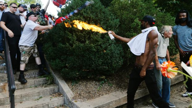 A counter-demonstrator uses a lighted spray can against a white nationalist demonstrator.