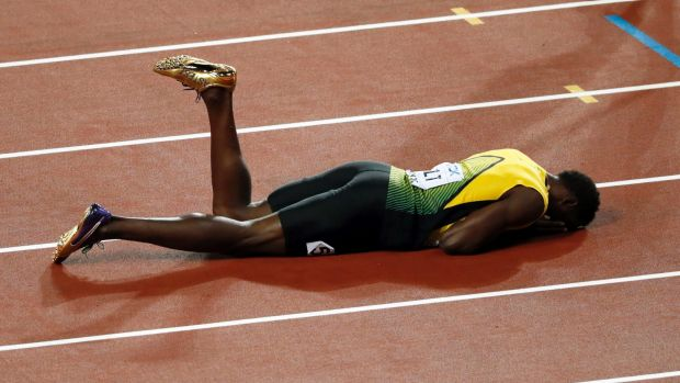 Dramatic finale: Usain Bolt lies on the track after pulling up injured in the final leg of the 4x100m relay at the World ...