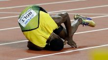 Jamaica's Usain Bolt falls on the track after suffering an injury in the men's 4x100-meter final during the World ...