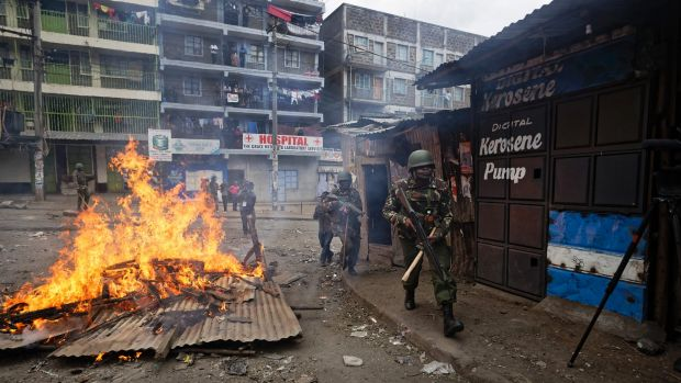 Riot police advance towards protesters during clashes in the Mathare area of Nairob.