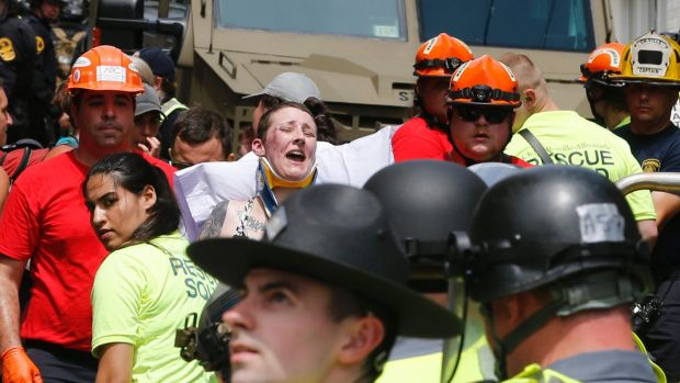 Rescue personnel help injured people after a car ran into a large group of protesters.