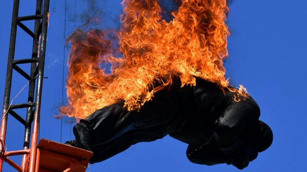 A stuntman on fire, dives from the high dive platform during the Western High Dive Show.